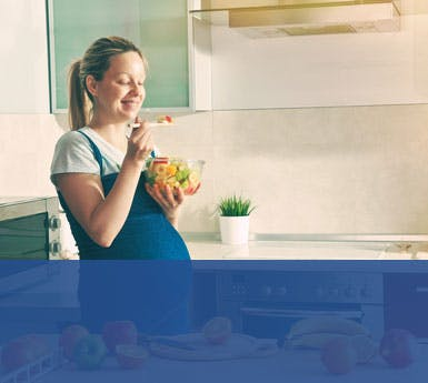 Pregnant woman eating in kitchen