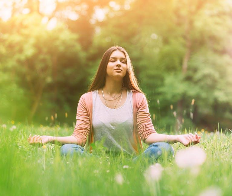 Kvinde sidder i fosterstilling på græs