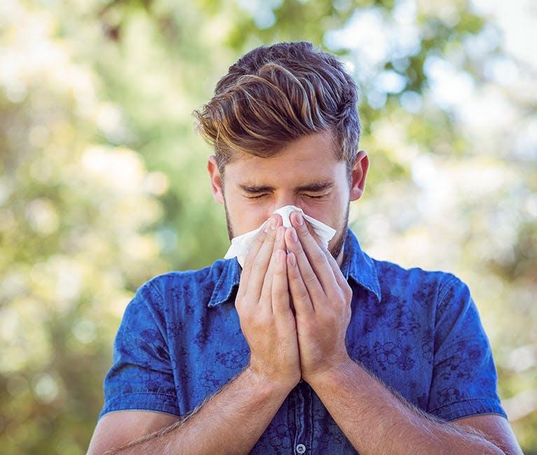 Ung mand pudser næse udenfor
