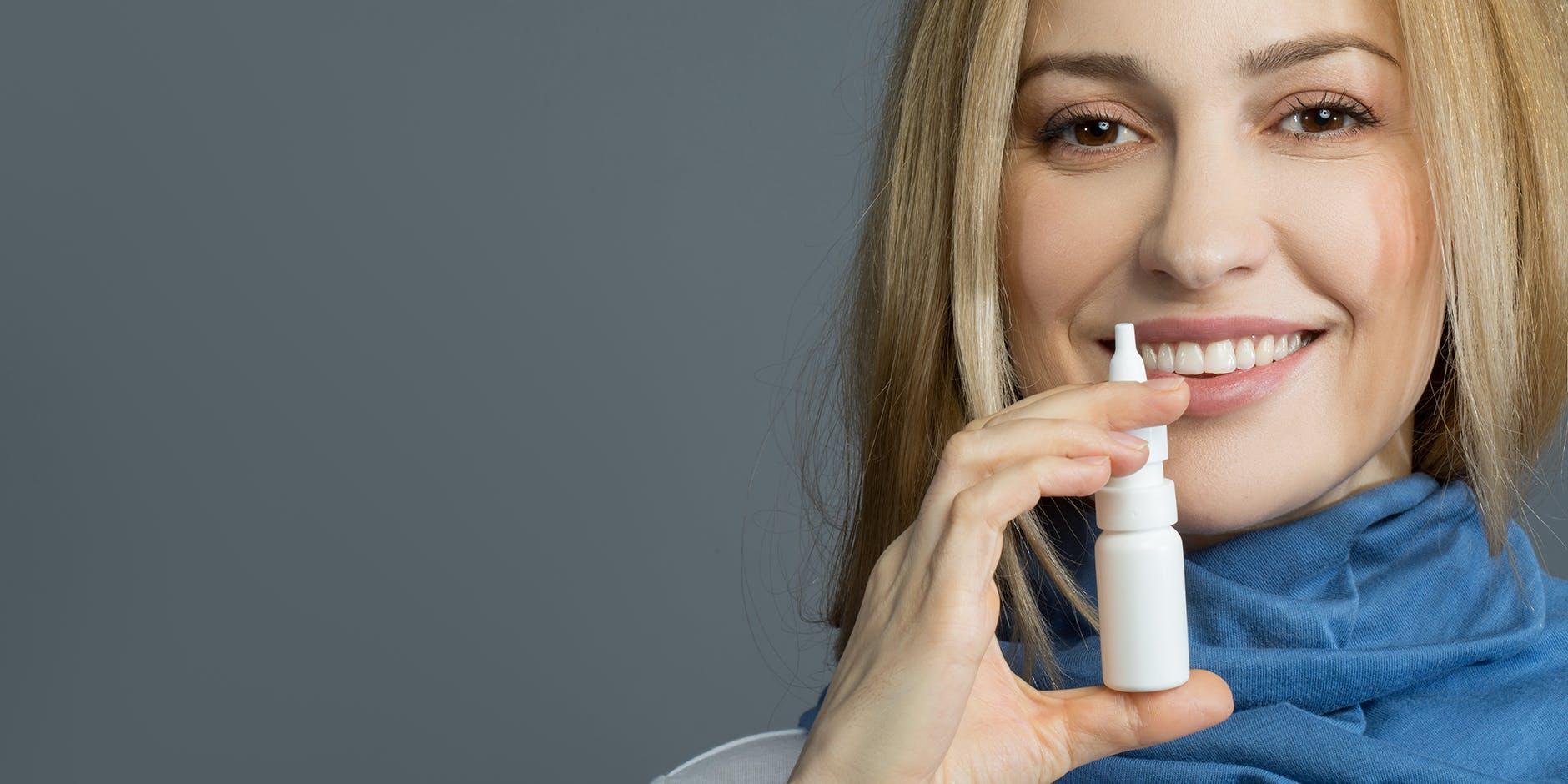 Kvinde bruger en næsespray med saltvand