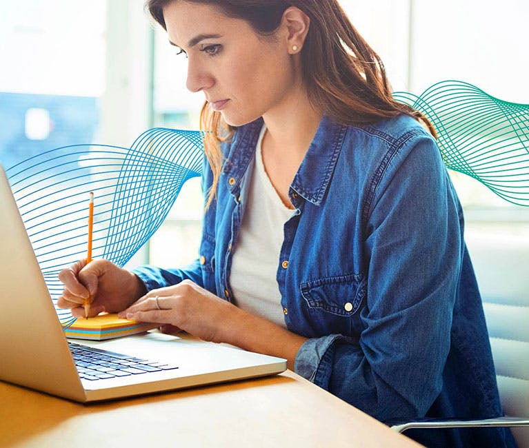 Set in an office environment with woman sitting at laptop writing notes