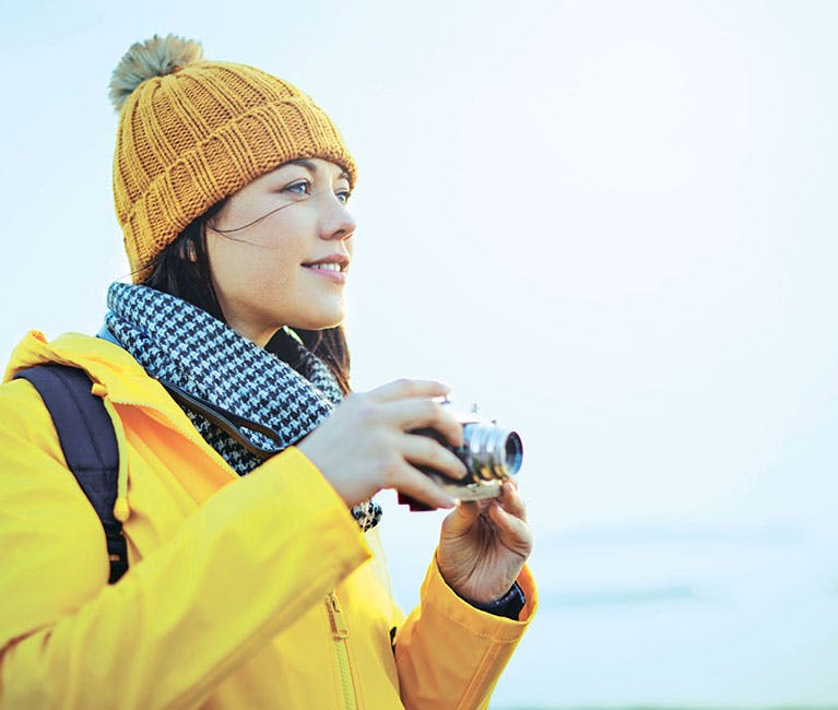 Woman wearing a hat coat and scarf is taking pictures of her surrounding landscape.