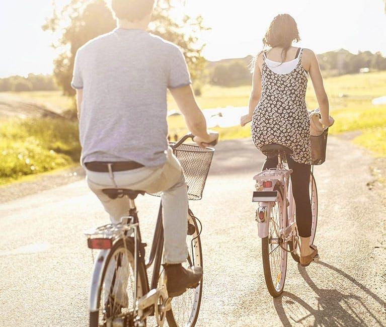 Ein Paar, das auf dem Land im Sommer Velo fährt