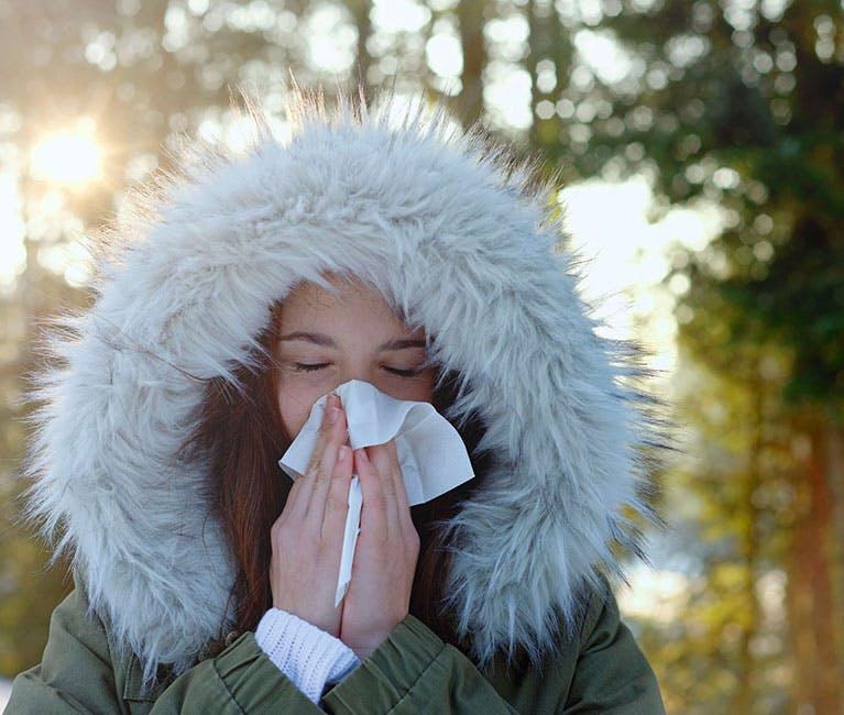 Frau putzt ihre verstopfte Nase in der kalten Winterluft.