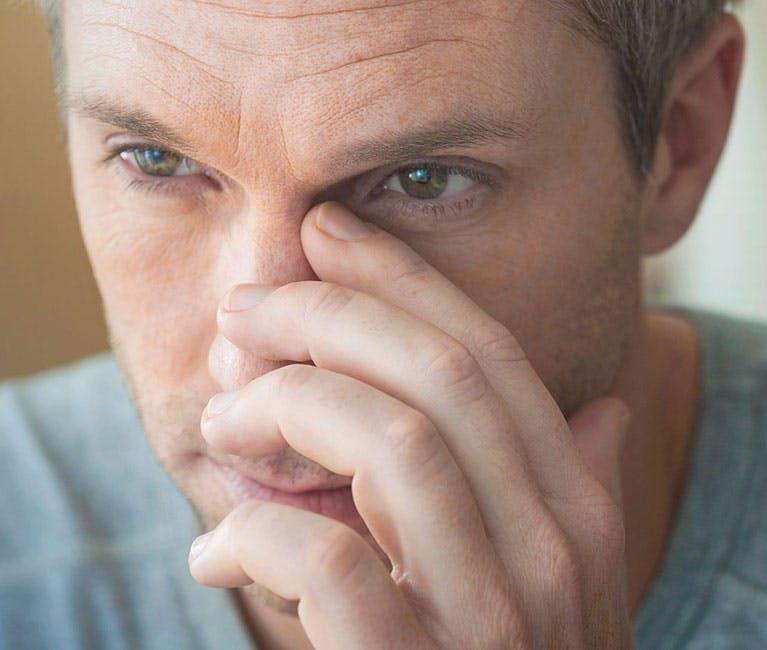 Mann, der unter einer verstopften Nase leidet, massiert seine Nebenhöhlen