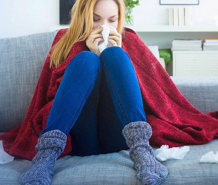 In eine Decke eingewickelte Frau zu Hause auf dem Sofa, die ihre Nase schnäuzt