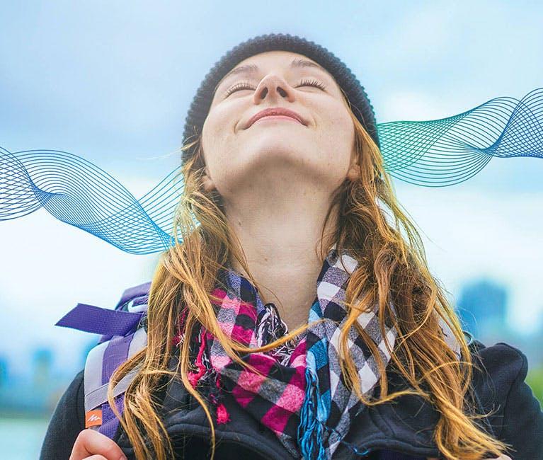 Frau, die mit Hut, Schal und erhobenem Kopf frische Luft einatmet