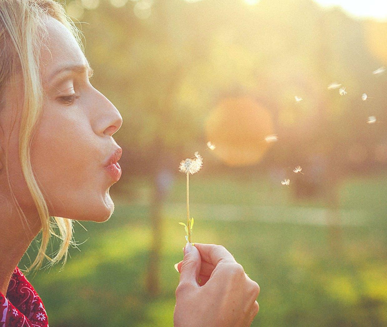 Eine Frau bläst auf eine Pusteblume, denn ihr Mittel gegen Heuschnupfen wirkt.