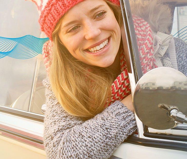 Grippe oder Erkältung: Frau lässt sich im offenen Autofenster den Fahrtwind um die Nase wehen