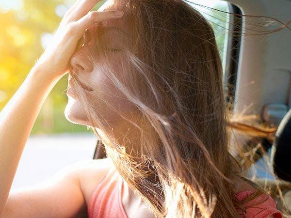 Nasenatmung: Frau mit Mütze und kariertem Schal atmet mit erhobenem Kopf frische Luft ein.