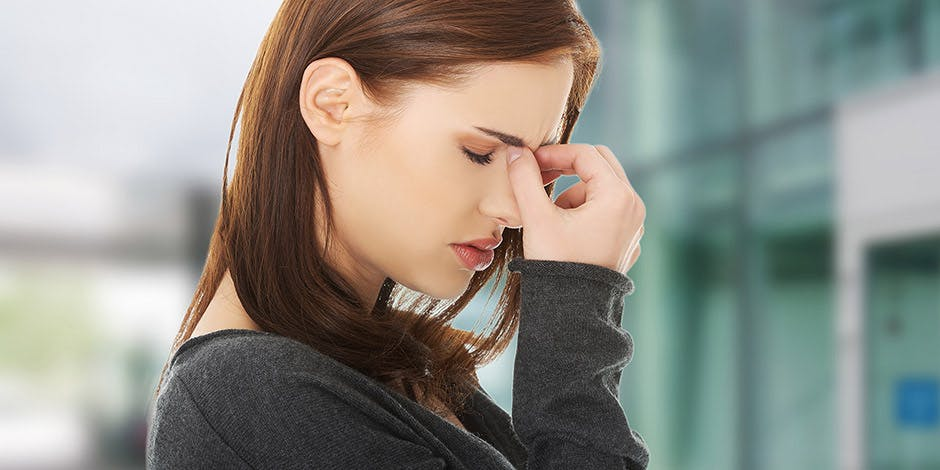 Woman suffering from nasal congestion holding nose