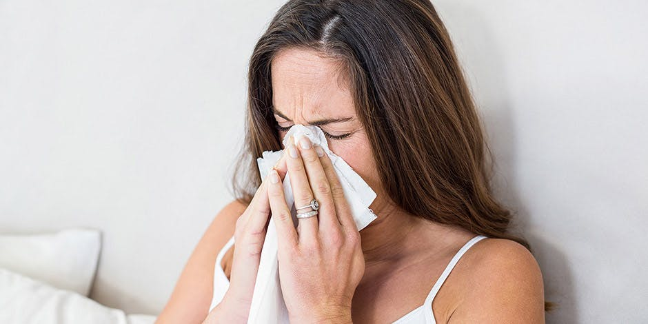 Woman dressed in white singlet blowing her nose with a tissue