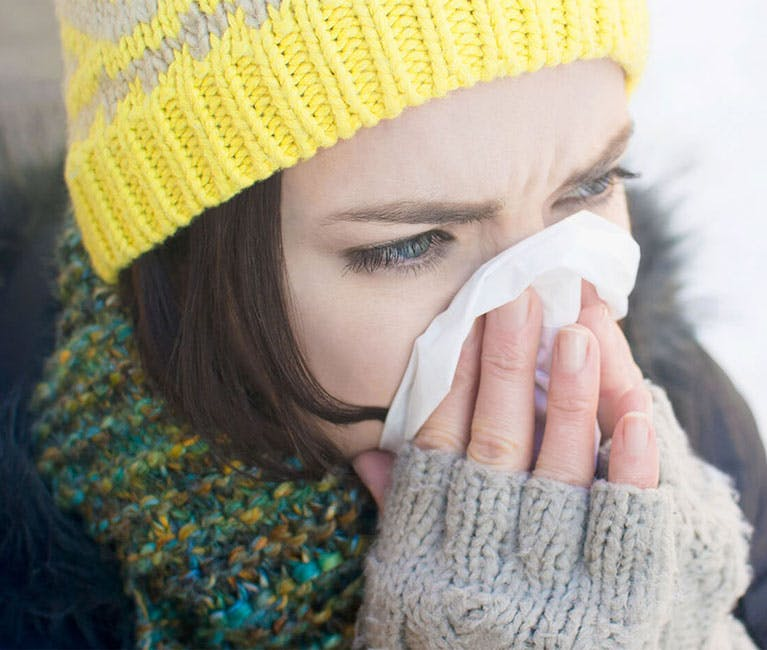 Woman dressed in winter clothing blowing her nose