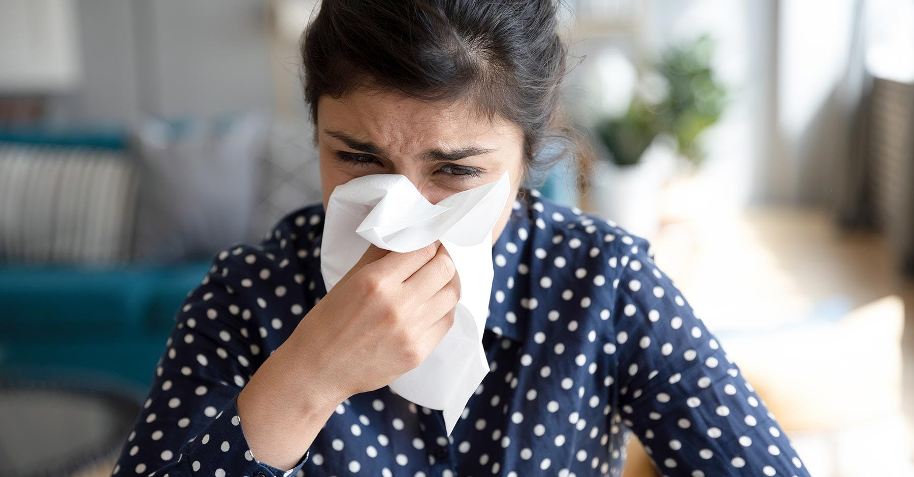 A black-haired woman is trying to blow her nose in a tissue