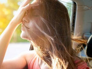 Passenger in car lifts face to open window and smoothes hair from her face