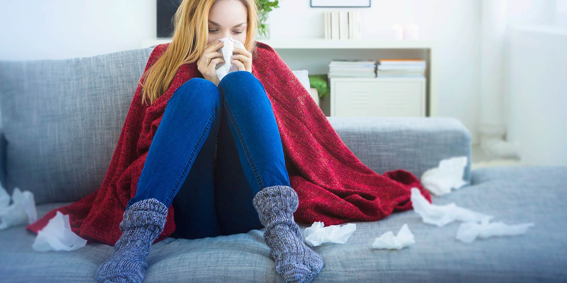 Woman at home on sofa wrapped in blanket blowing her nose