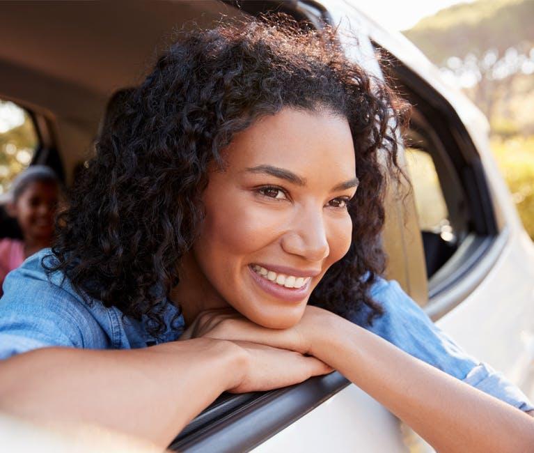 Une femme profite du soulagement du rhume, du nez bouché et du rhume des foins dans sa voiture, la fenêtre ouverte