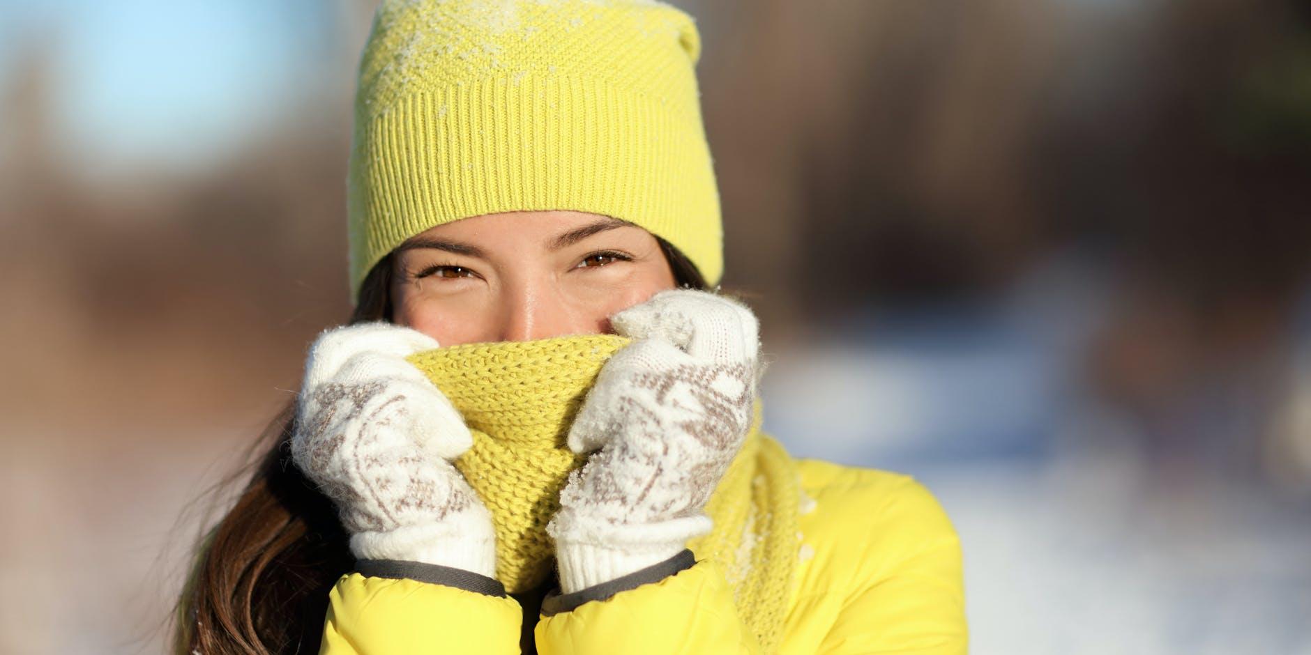 Une femme se couvre le nez avec son écharpe après avoir utilisé les remèdes recommandés contre la congestion nasale.