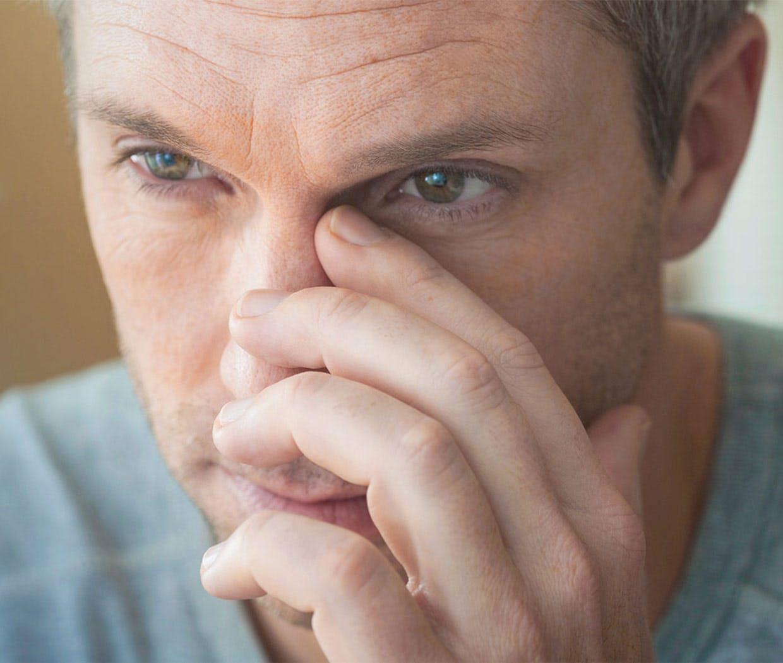 Homme qui ronfle par le nez à cause des sinus bouchés.