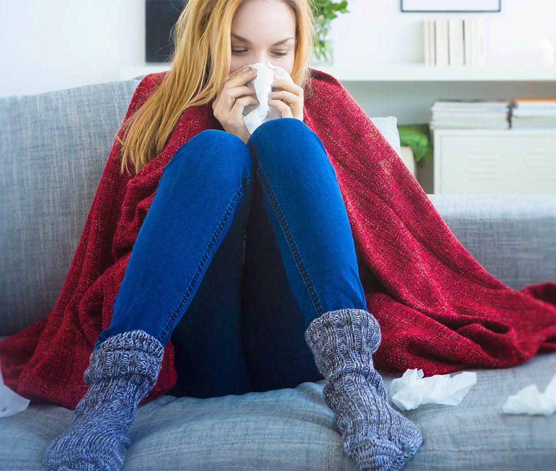 Kanapén ülő nő takaróba burkolózva fújja az orrát