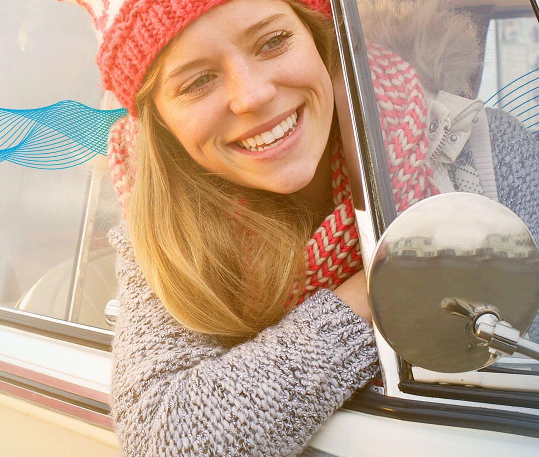 Nő mosolyog autó ablakán kihajolva