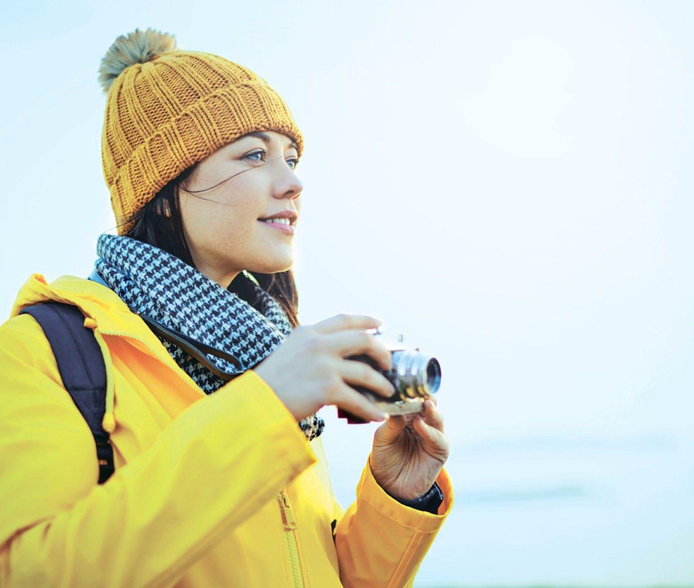 Kvinne med hatt, jakke og skjerf tar bilder av landskapet.