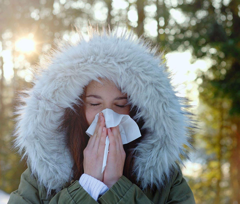 Kvinne med tett nese, og som pusser nesen i den kalde vinterluften.