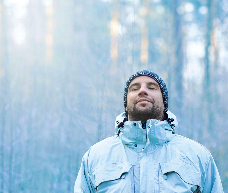 En mann med varm hatt og jakke puster inn kald vinterluft