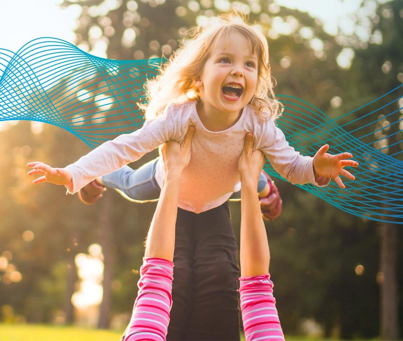 Mammaen ligger på gresset og holder datteren som et fly, barnet smiler