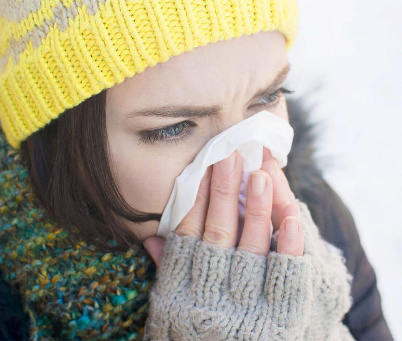 Kvinne i vinterklær pusser nesen
