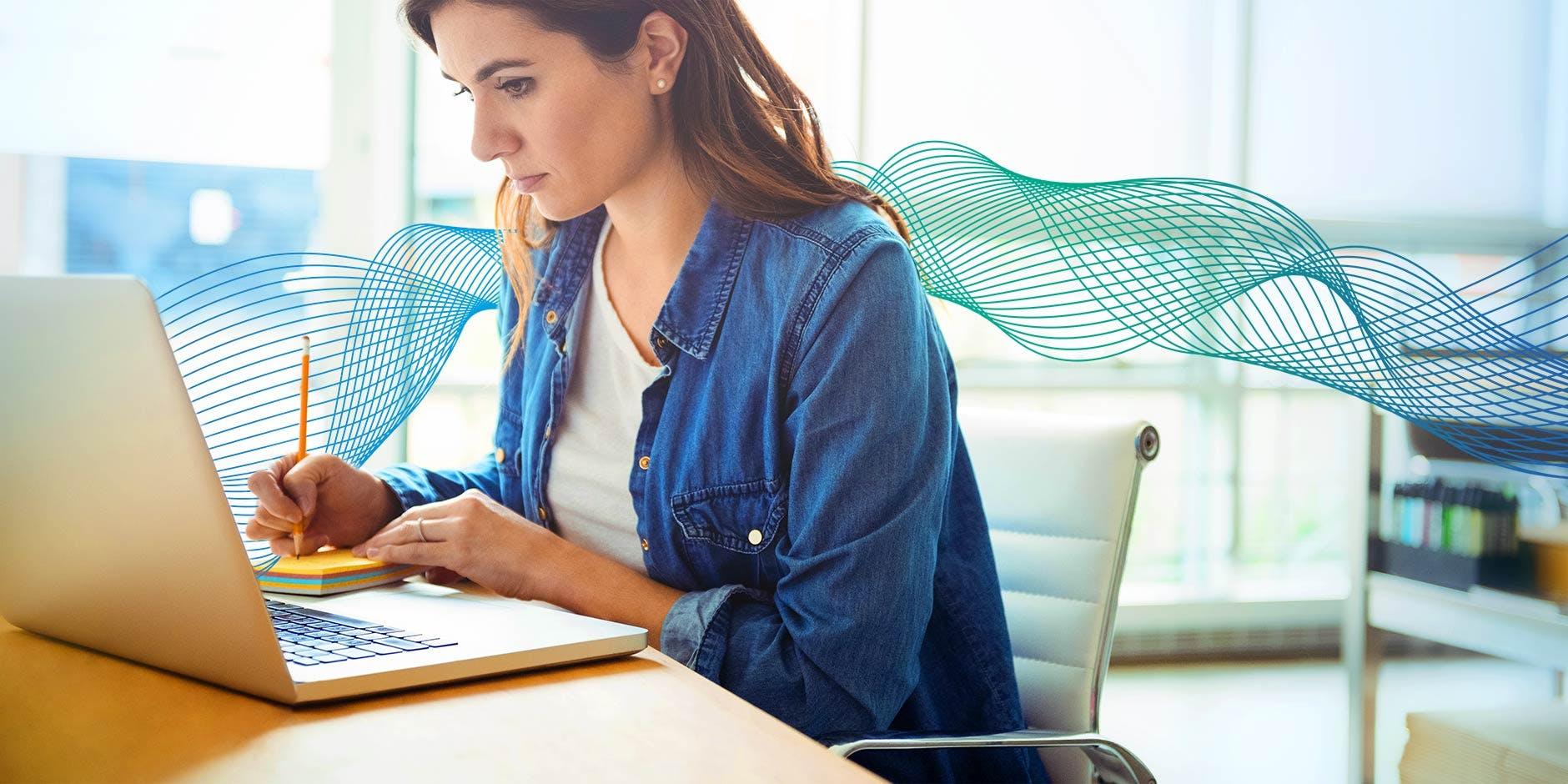 i et kontormiljø hvor en dame sitter ved laptopen og tar notater