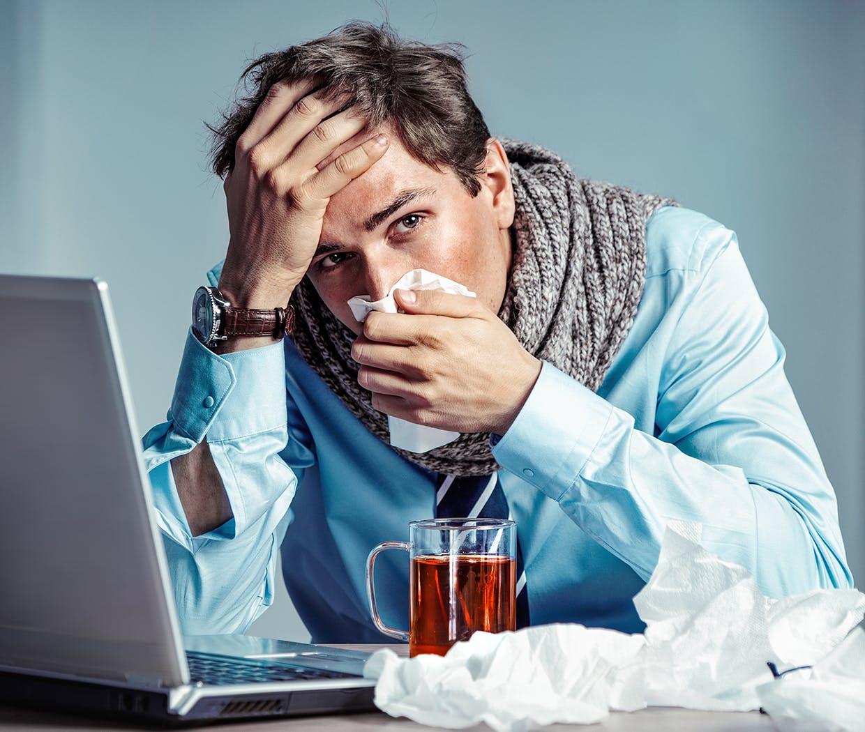 Bărbat aflat la serviciu și care își suflă nasul și nu se simte bine