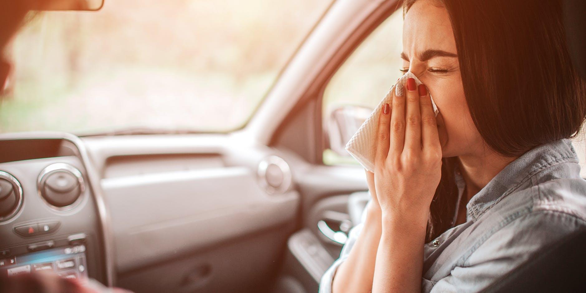 Femeie aflată în mașină și care își suflă nasul
