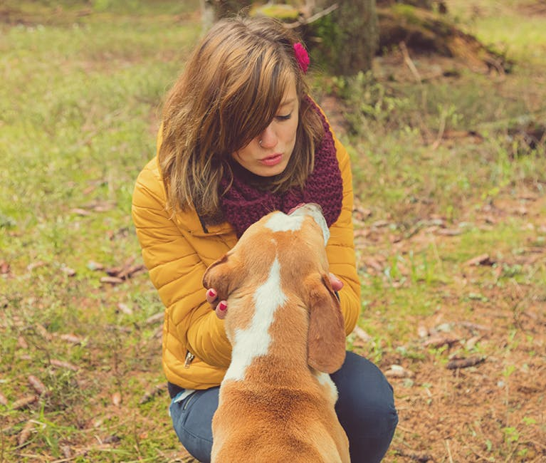 Femeie care se joacă cu un câine în parc