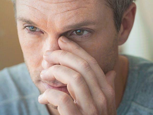 Мужчина, страдающий заложенностью носа, массажирует носовые пазухи.
