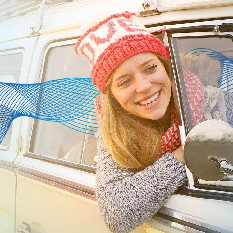 En kvinna ler med huvudet utanför bilfönstret
