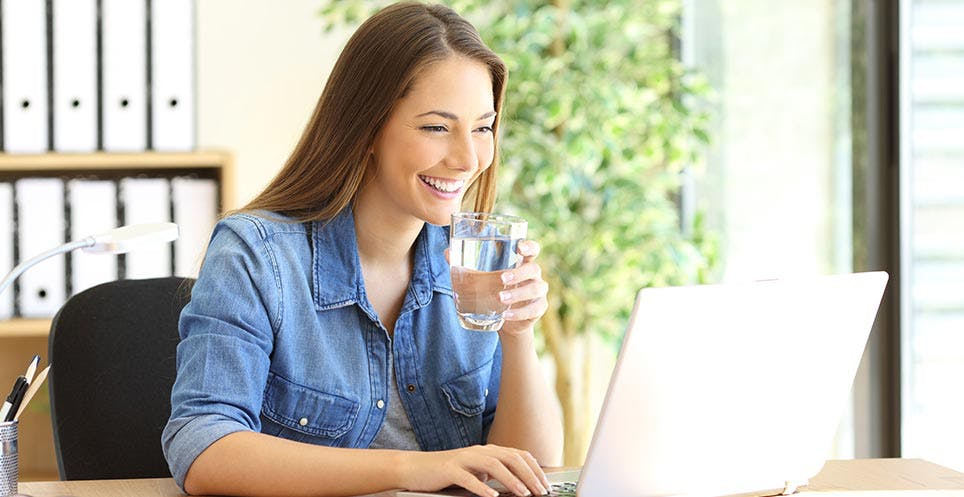 Woman drinking water and looking at her laptop