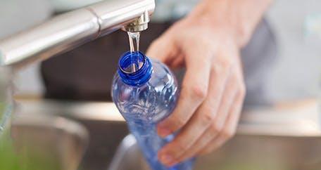 filling up plastic water bottle