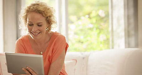 Women using an iPad while sitting on a couch