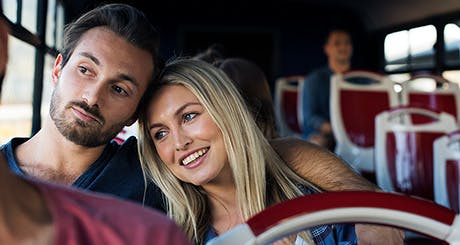 Young couple traveling together on a bus.