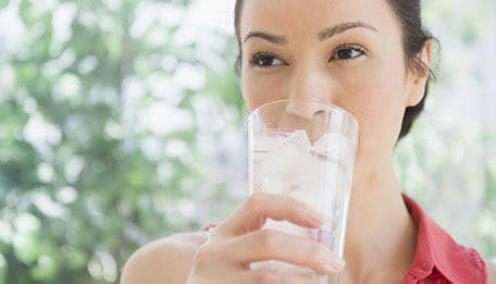 woman drinking a glass of iced water