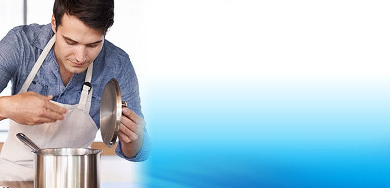 Man smelling a pot of food that he is cooking