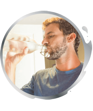 man drinking a glass of iced water