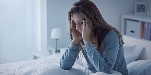 Young woman sitting on her bed looking stressed about insomnia.