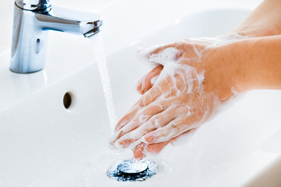 Woman washing her hands in sink with soap.