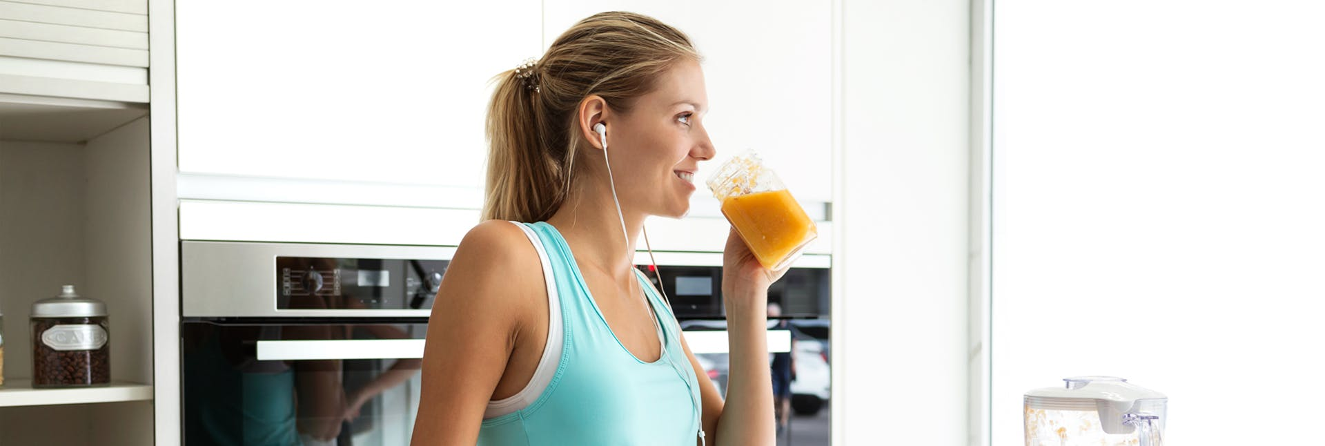 Athletic woman drinking a smoothie and listening to music