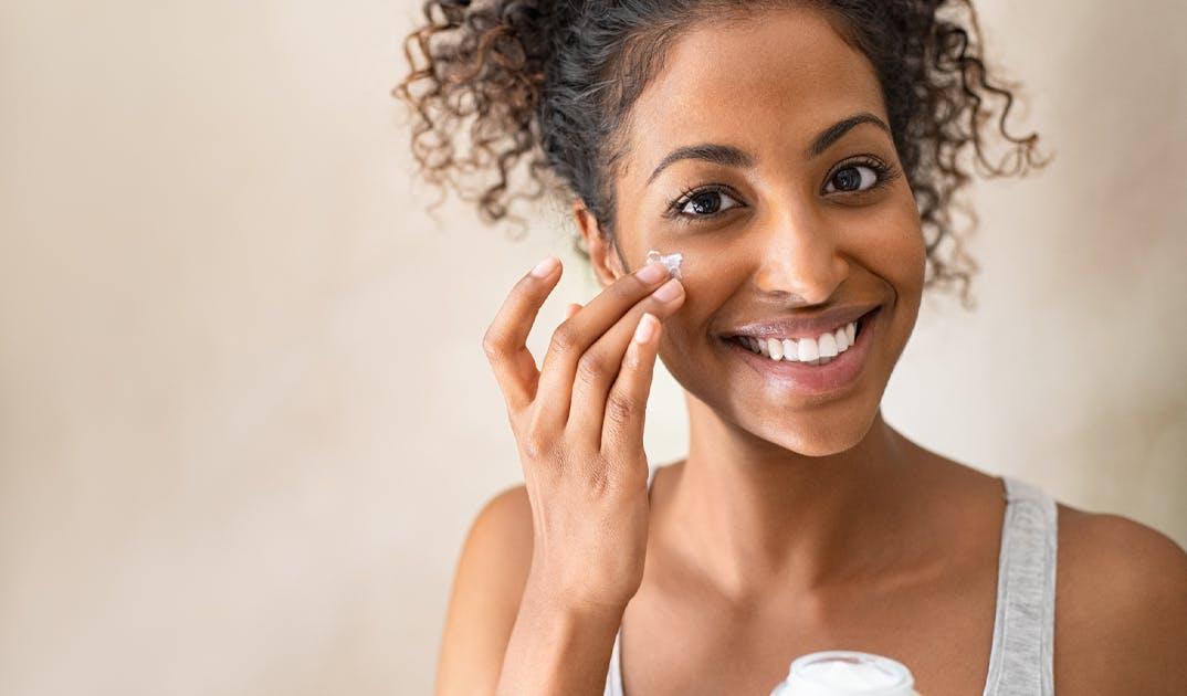 woman rubbing skin moisturizer into her cheek