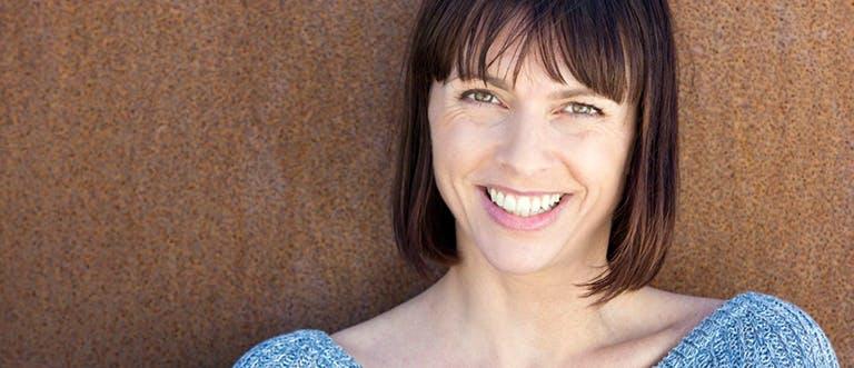 Žena se usmívá před hnědou zdí