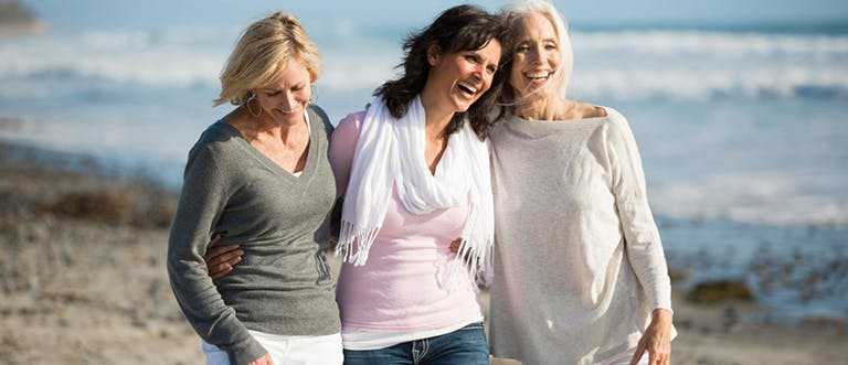 Tři starší dámy se procházejí po pláži.
