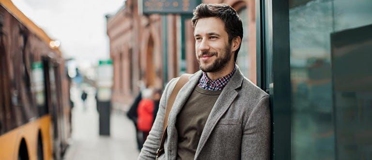 Muž s vousy stojící na zastávce autobusu